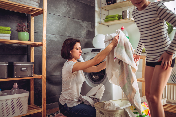 Woman putting clothes in a washing machine