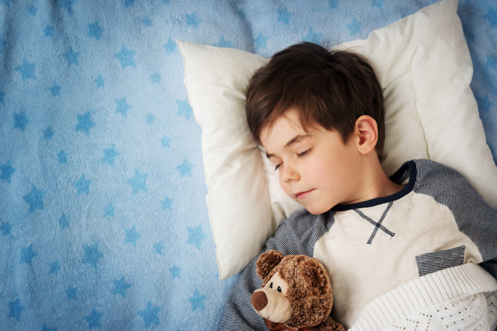 six years old child sleeping in bed with alarm clock
