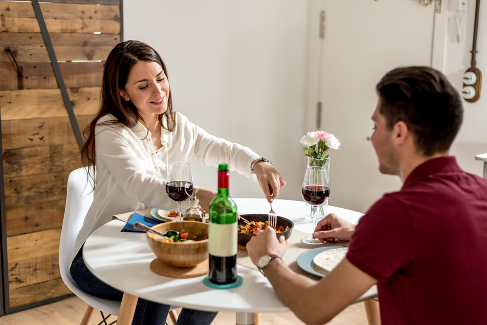 Young couple having dinner in new home