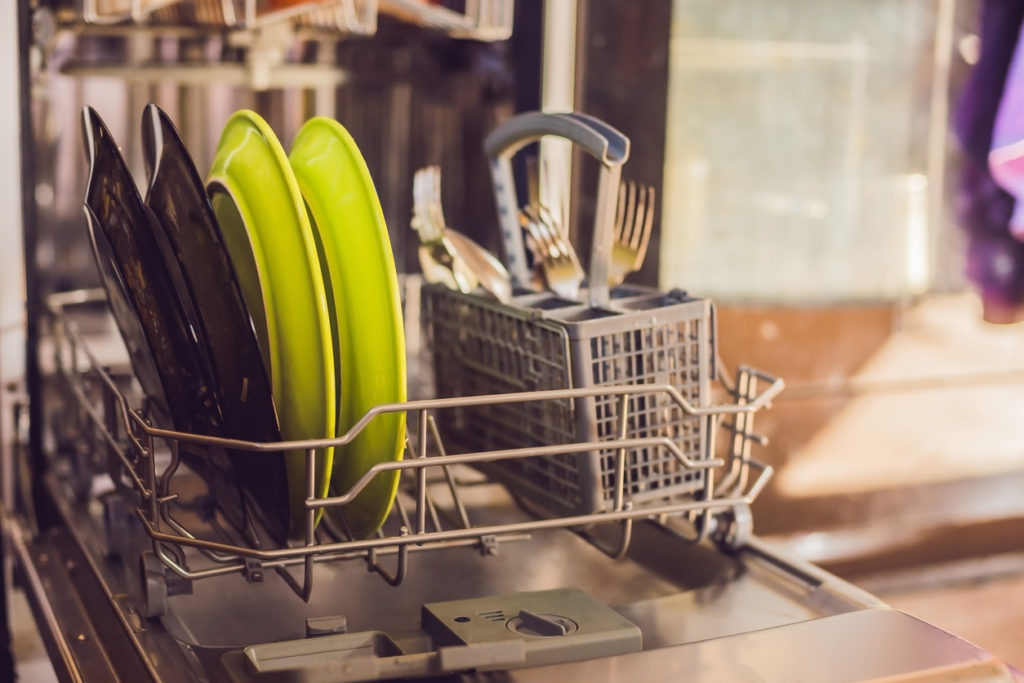 Dishwasher with dirty dishes. Powder, dishwashing tablet and rinse aid. Washing dishes in the kitchen