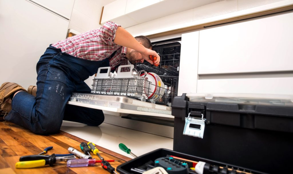 Professional fixing a broken dishwasher